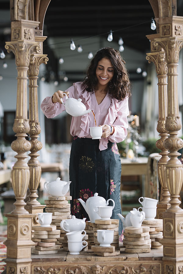 Smiling woman pouring black tea in cup standing near beautiful composition of tea set on wooden stand.